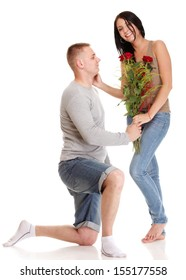 Loving Portrait of beautiful young happy smiling couple isolated - man down on his knee giving his girlfriend a rose and the girl isolated on white