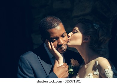 Loving pretty girl or beautiful bride kissing tenderly handsome man or african American groom on sunny wedding day, married couple, outdoors on dark background