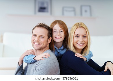 Loving pretty little redhead girl with her parents hugging them with both arms as they sit back to back smiling at the camera