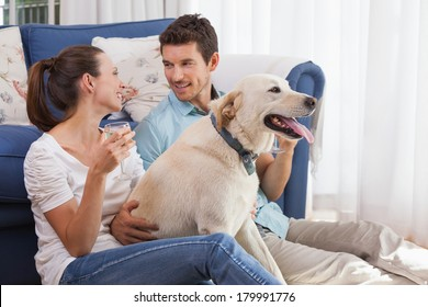 Loving relaxed young couple with wine glass and pet dog sitting in living room at home