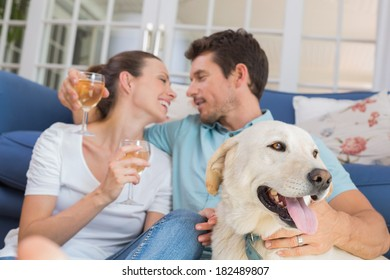 Loving relaxed young couple with wine glasses and pet dog sitting in living room at home