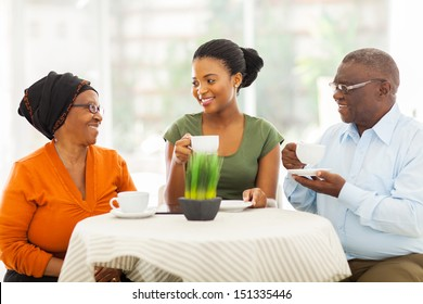 loving senior african parents having coffee with daughter indoors