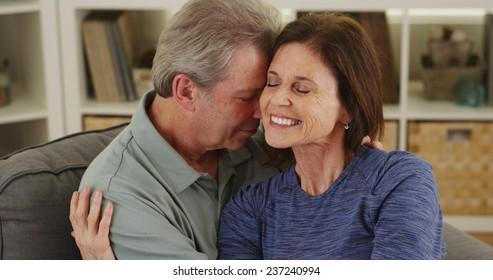 Loving senior couple cuddling on couch