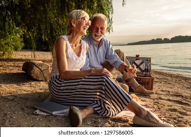 Loving senior couple enjoying a leisurely picnic by the river