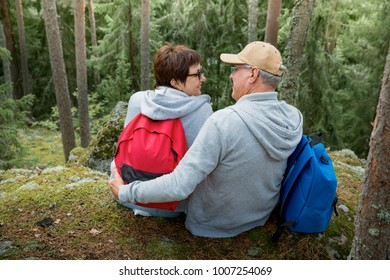 Loving senior couple hiking, sitting on the top of rock in forest, exploring. Active Mature man and woman hugging and Happily smiling. Scenic view. Healthy lifestyle. Finland.