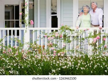 Loving senior couple at home on verandah overlooking garden