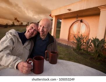 Loving senior couple in jackets with mugs outside