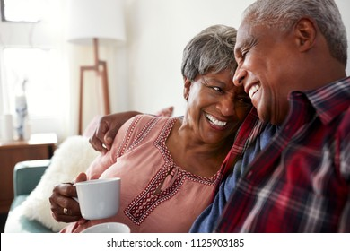 Loving Senior Couple Sitting On Sofa At Home Relaxing With Hot Drink