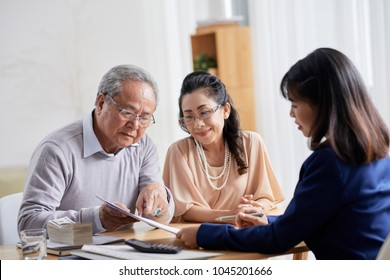 Loving senior couple sitting at spacious office of estate agent and asking questions concerning terms of purchase agreement