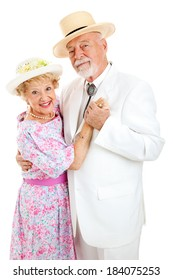 Loving senior couple in Southern style clothing dancing together.  White background.