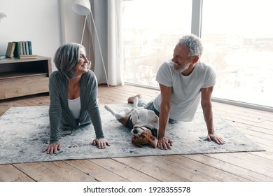 Loving senior couple in sports clothing doing yoga and smiling while spending time at home with their dog