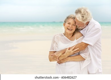Loving senior male and female Caucasian couple in white casual clothes together on a tropical vacation beach