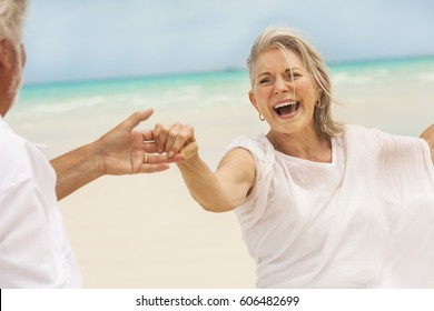 Loving senior male and female Caucasian couple in white casual clothes dancing together on a tropical beach