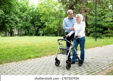 Loving senior man keeping company to his loving wife in the park while helping her to gain walking confidence