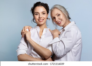 Loving senior mother hugging adorable young daughter portrait. Two beautiful woman different age wearing white shirt. Closeness and trust in family relation. Support and help from parent