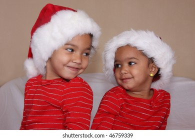 loving sisters wearing christmas caps looking at each other smiling