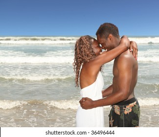 Loving Smiling Couple on the Beach With Arms Around Eachother
