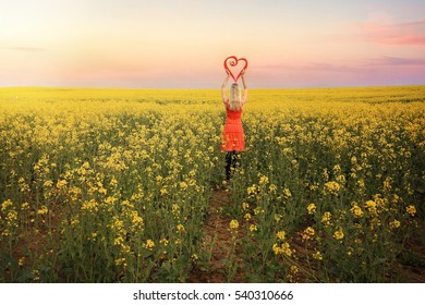 Loving springtime in Young, Hilltops Region, Country NSW.  Female standing with a red heart in flowering canola as far as the eye can see