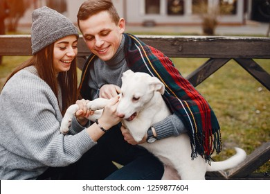 loving and stylish couple in a spring city plaing with dog