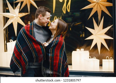 loving and stylish couple standing in a street near wall with plaid