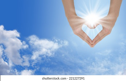 Loving the Sunshine  -  Female hands forming a heart shape capturing the sunburst behind on a wide blue sky and fluffy cloud background