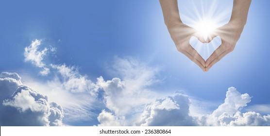 Loving the Sunshine  -   Female hands forming a heart shape capturing the sunburst on a blue sky and fluffy cloud background