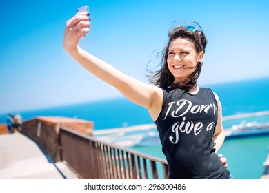Loving to take pictures of herself, girl smiling and being happy while making selfie.