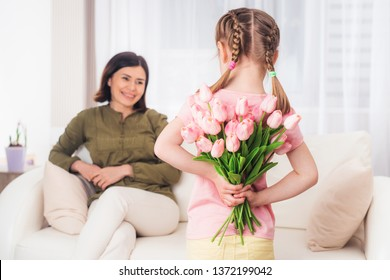 Loving teen little girl preparing surprise for mother on Mothers day, 12th may