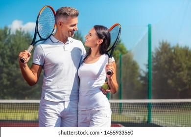 Loving tennis greatly. Good-looking happy couple holding rackets while loving tennis greatly