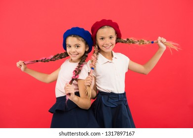 Loving their new style. Small children with long hair plaits. French style girls. Cute girls having the same hairstyle. Fashion girls with tied hair into braids. Little kids wearing french berets.