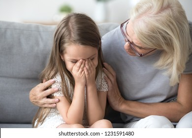 Loving understanding old grandma embracing little crying girl comforting upset granddaughter, senior caring grandmother hugging child consoling kid in tears, grannys empathy support for grandchild