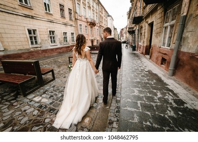A loving wedding couple are walking back along the streets of the city of Lviv.