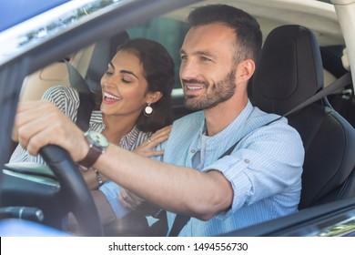 Liebende Frau umarmt. Liebende lächelnde Ehefrau umarmt ihren hübschen bärtigen Mann, der Auto fährt