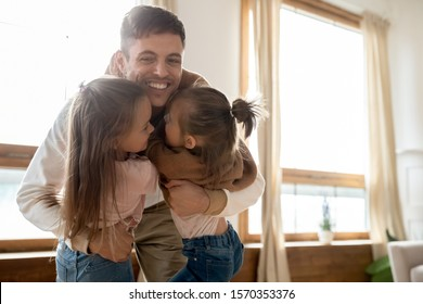 Loving young adult parent father hugging sweet cute small kids daughters at home, happy dad and little funny children girls embracing bonding enjoy reunion meeting spend leisure time together indoor