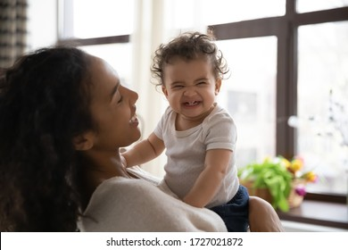 Loving young african American mother hold in arms cute funny infant toddler showing first teeth, caring happy biracial mom hug embrace smiling little baby girl child, motherhood, childcare concept