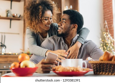 Loving young african-american couple using smartphone in kitchen