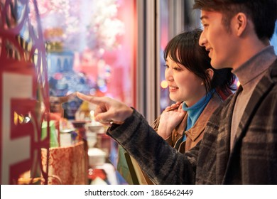 loving young asian couple looking at shop window and talking happy and smiling