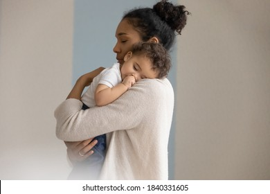 Loving young biracial mother hold in hands embrace small newborn baby child. Caring african American mom lean to chest hug cuddle little infant child, enjoy tender close family moment together.