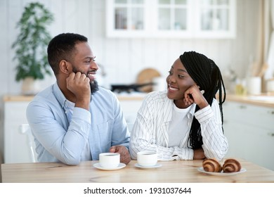 Loving Young Black Couple Drinking Coffee With Croissants And Bonding In Kitchen. African American Sweethearts Sitting At Table And Looking At Each Other With Love, Enjoying Spending Time Together