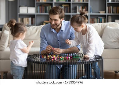 Loving young Caucasian father engaged in funny creative activity making bracelets with little daughters, happy dad have fun string thread wooden colorful beads play with small girls children