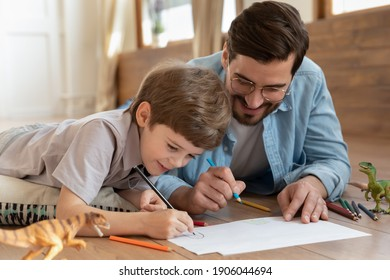 Loving young Caucasian father lying on floor at home have fun painting with little 7s son together. Happy playful dad drawing in album with excited small boy child on weekend at home. Hobby concept.