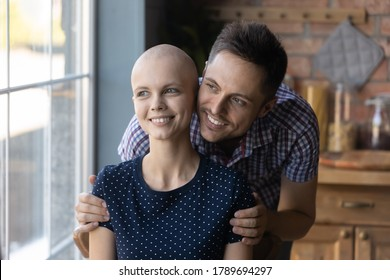 Loving young Caucasian husband hug comfort optimistic sick cancer patient wife, look in distance dream of happy future recovery together, caring man embrace support ill woman, oncology concept