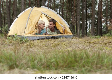 Loving young couple camping in forest