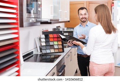 Loving young couple choosing kitchen furniture materials for a their apartment. Focus on man