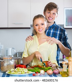 Loving young couple cooking vegetables in domestic kitchen. Focus on woman