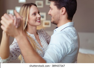 Loving young couple dancing together at home to celebrate a special occasion smiling into each others eyes