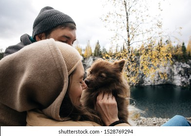 loving young couple with a dog in hats and brown coats cuddling in the mountains in beautiful autumn