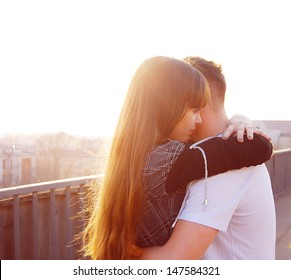 A loving young couple embracing on the bridge
