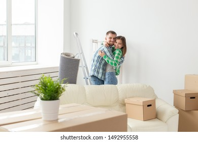 Loving young couple embracing rejoicing in moving to their new home. The concept of moving and housewarming of young family.