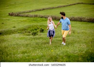Loving young couple enjoying a walk through grass land on a summer day - Shutterstock ID 1655294635